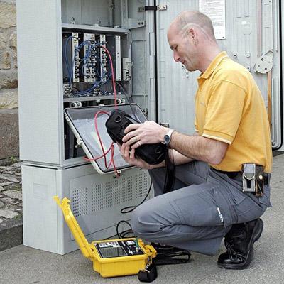 Kabel Deutschland Techniker an einem Kabel Verteilerkasten